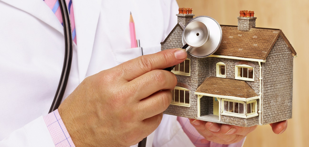 Doctor holding stethoscope to model house.