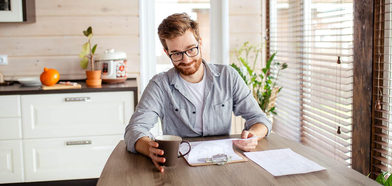 man reviewing paperwork in kitchen