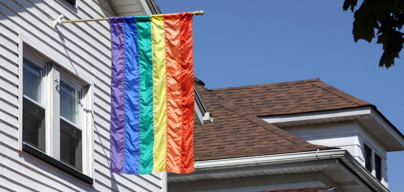 A colorful flag hanging from the side of a house