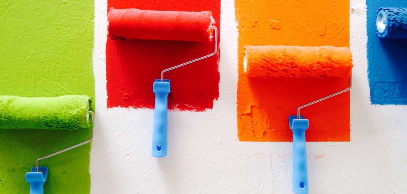 Four paint rollers with different colors