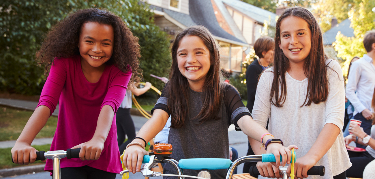 three friend riding bikes and skooters on neighborhood street