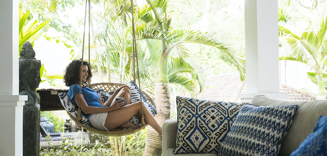 Woman sitting in hanging chair in vacation home