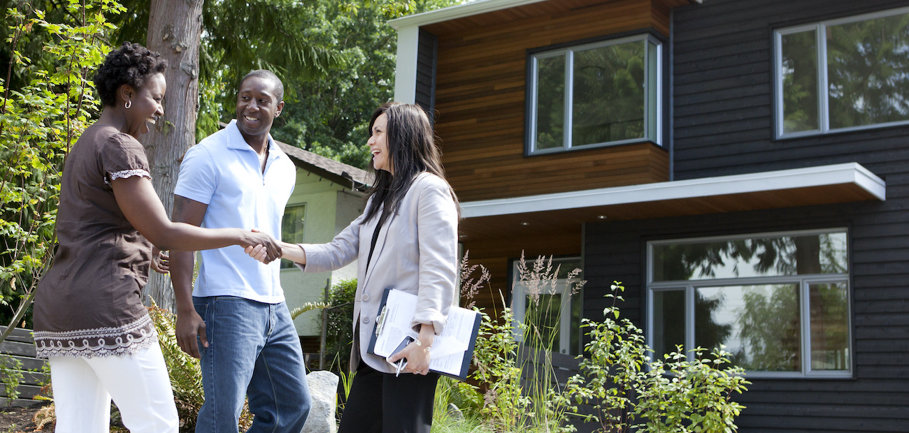 African American couple meeting real estate agent to look at home