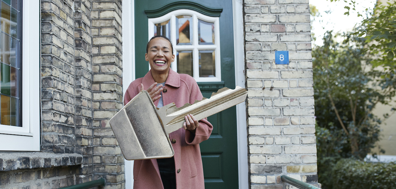 Woman holding large key in front of home