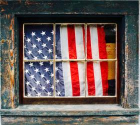 American flag behind window with peeling paint